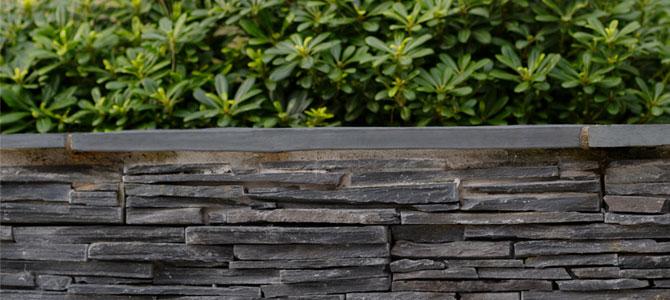 Stonepanel Laja Jet Dark instalado en el muro de un jardín